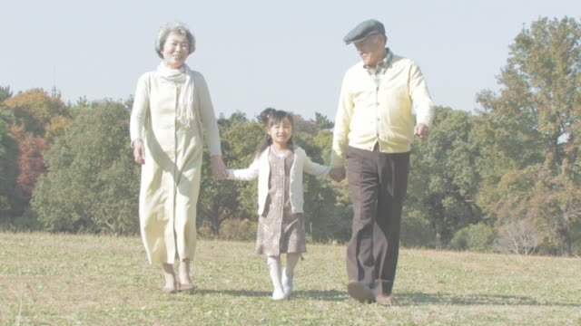 Grandparents and granddaughter walking hand in hand