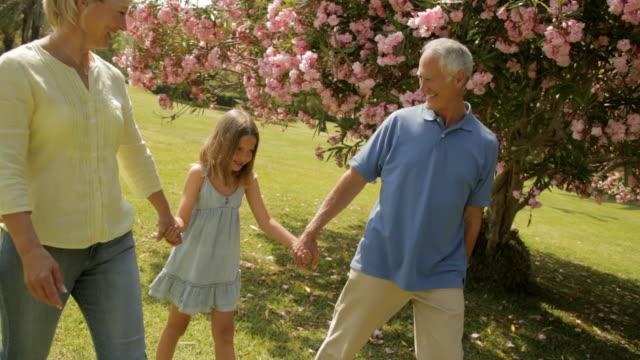 vídeos y material grabado en eventos de stock de grandparents and granddaughter walking in park - casados