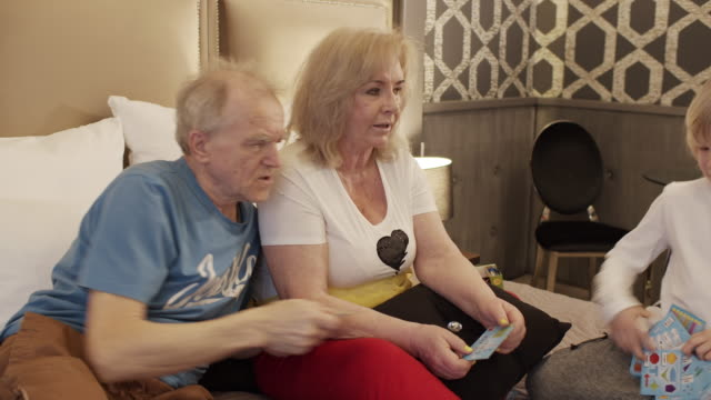 stockvideo's en b-roll-footage met grootouders en kleinzoon met plezier spelen bordspel. - spelletjesavond