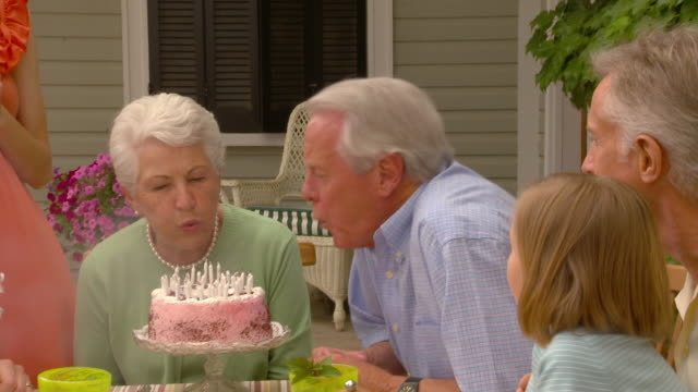 ms grandparents blow out candles on birthday given by family sitting around outdoor table / richmond, virginia - 50 59 years stock videos & royalty-free footage