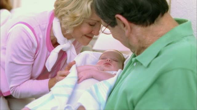vídeos y material grabado en eventos de stock de ms grandparents caressing newborn baby girl (0-1 months) / tampa, florida, usa - bebés 0 1