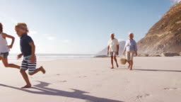 Grandparents Carrying Picnic Basket On Beach As Grandchildren Run Ahead