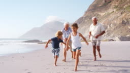 Grandparents Chasing Grandchildren Along Beach On Summer Vacation