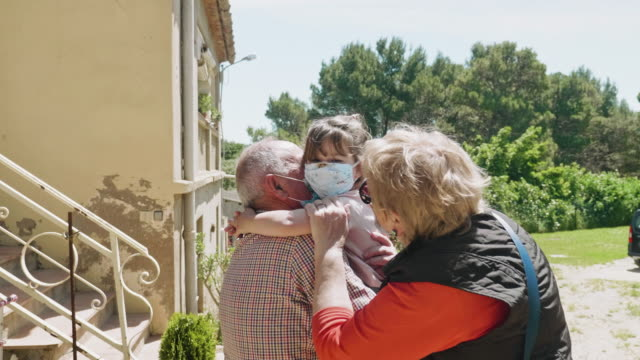 grandparents embracing their grandfather after a few weeks not seen her during the pandemic - visit stock videos & royalty-free footage