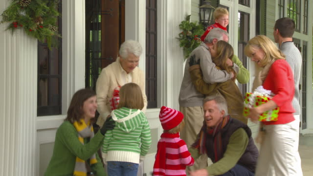 ms grandparents greeting family with christmas presents at front door of home / richmond, virginia - grandfather stock videos & royalty-free footage