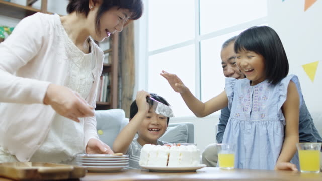 Grandparents Helping Boy Cut Cake