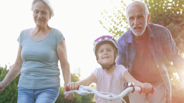 slo mo grandparents helping granddaughter ride the bike for the first time and cheering for her - protezione video stock e b–roll