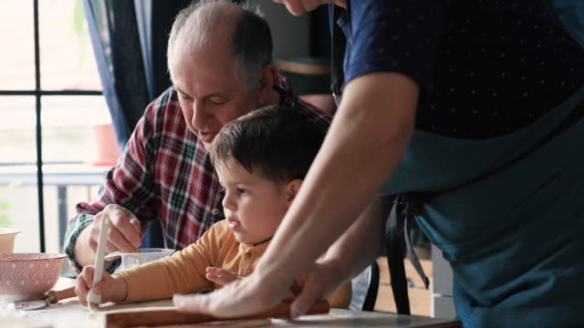 grandparents in kitchen with grandson making cheese rolls together - nipote maschio video stock e b–roll