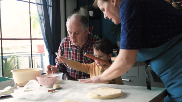 grandparents in kitchen with grandson making cheese croissantstogether - grandchild stock videos & royalty-free footage