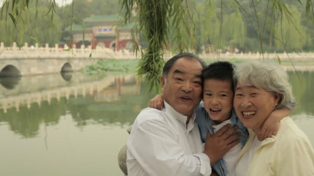stockvideo's en b-roll-footage met ms grandparents laughing with their grandson in a park/ beijing, china - chinese etniciteit