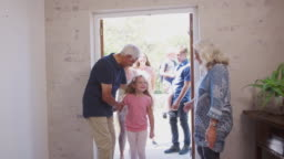 Grandparents Open Front Door Of House To Welcome Multi-Generation Family On Visit
