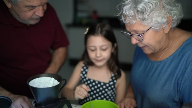 grandparents preparing coffee with they granddaughter at home - cucina domestica video stock e b–roll