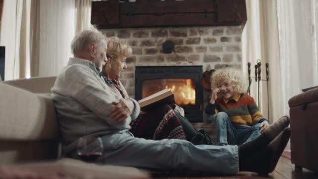 vídeos de stock e filmes b-roll de grandparents reading a story to grandson - lareira