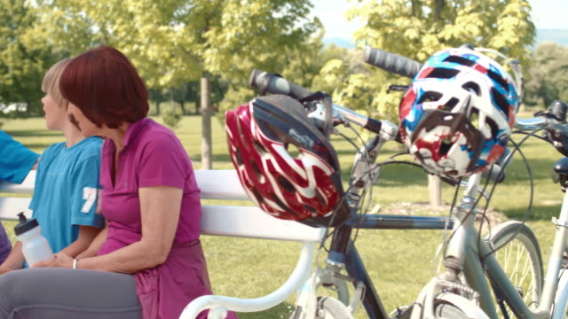 slo mo grandparents resting on a bench with their grandchildren after cycling - helmet stock videos & royalty-free footage