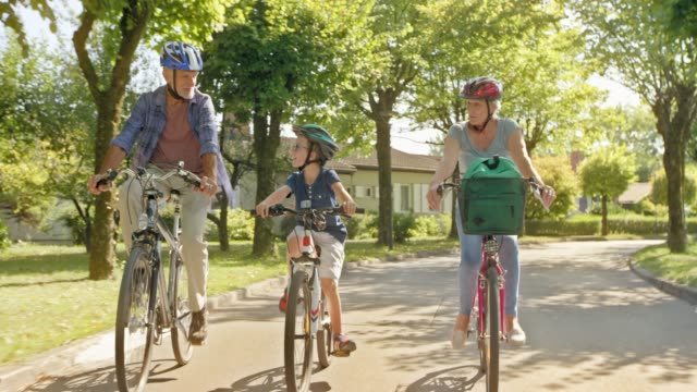 ds grandparents riding bikes with their grandson in a nice neighborhood - three people stock videos & royalty-free footage