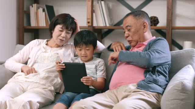 Großeltern saßen mit ihren Enkel mit einem digitalen tablet