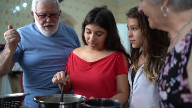 vídeos de stock, filmes e b-roll de os avós ensinando seu neto como cozinheiro - preparando comida