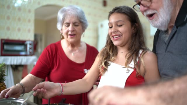 grandparents teaching their grandchild how to cook - granddaughter stock videos & royalty-free footage