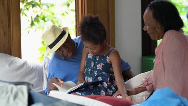 vídeos de stock, filmes e b-roll de avós, ensinando sua neta a ler em casa - neta