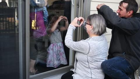 far-och morföräldrar besöker familjen barn på balkong under covid-19 - besök bildbanksvideor och videomaterial från bakom kulisserna