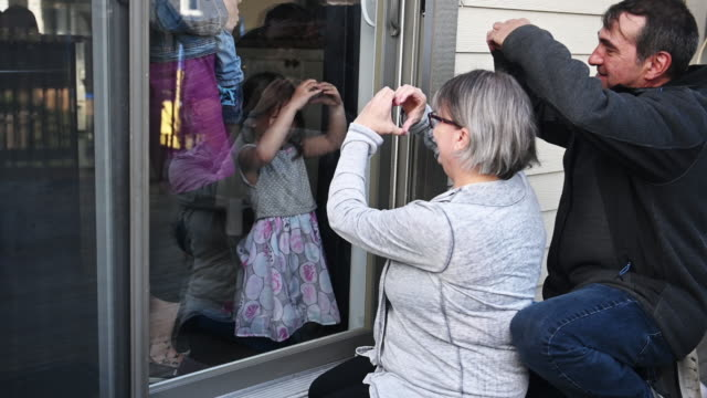 grandparents visiting family kids on balcony during covid-19 - waving stock videos & royalty-free footage