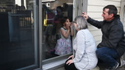 Grandparents visiting family kids on balcony during covid-19