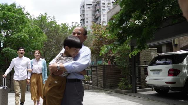 vídeos de stock, filmes e b-roll de grandparents que acolhe a família na frente da casa - etnia oriental