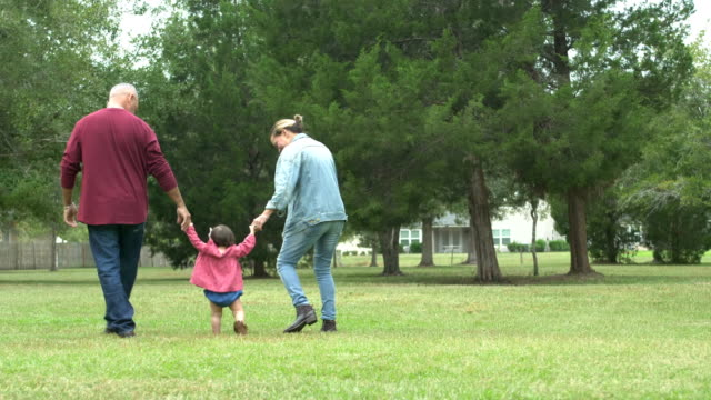 grandparents with baby learning to walk - diversity stock videos & royalty-free footage