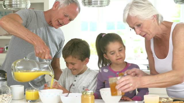 grandparents with grandchildren making breakfast in kitchen - orange juice stock videos & royalty-free footage