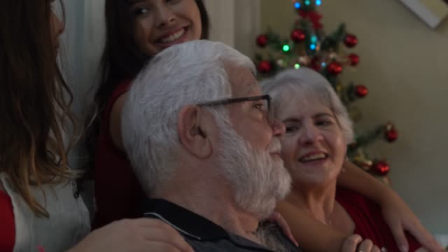 vídeos de stock e filmes b-roll de grandparents with granddaughters celebrating christmas dinner - cantar