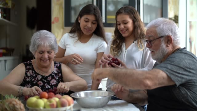 grandparents with their grandchild in the kitchen at home - ethnicity stock videos & royalty-free footage
