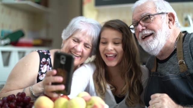 ビデオ チャットを自宅に持つ自分の孫娘と祖父母 - コミュニケーション形態点の映像素材/bロール