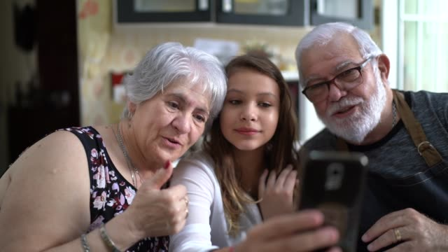 grandparents with their granddaughter having video chat at home - grandparents stock videos & royalty-free footage