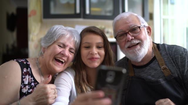 großeltern mit ihrer enkelin in der küche zu hause nehmen selfies - großvater stock-videos und b-roll-filmmaterial