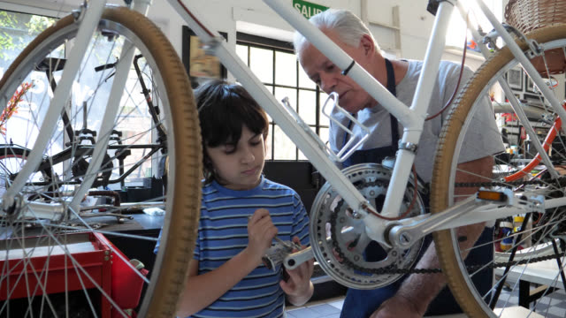 grandson adjusting a pedal on a bicycle and grandfather teaching him - communication stock videos & royalty-free footage