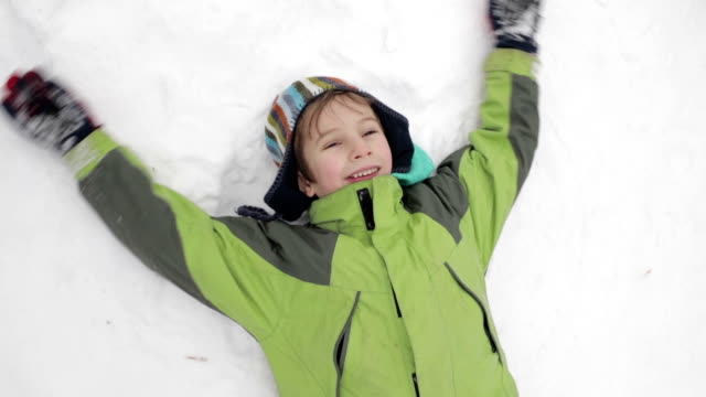 grandson and grandmother making snow angel - cap stock videos & royalty-free footage