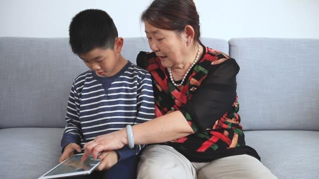 stockvideo's en b-roll-footage met kleinzoon en oma spelen go game met behulp van digitale tablet - spelletjesavond