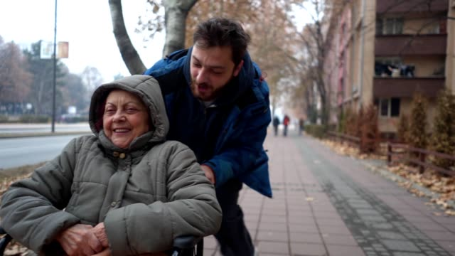 grandson and his grandmother in a wheelchair enjoying their time together - pushing stock videos & royalty-free footage