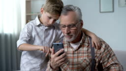 Grandson explaining grandpa how to use smartphone, boy feels to be important
