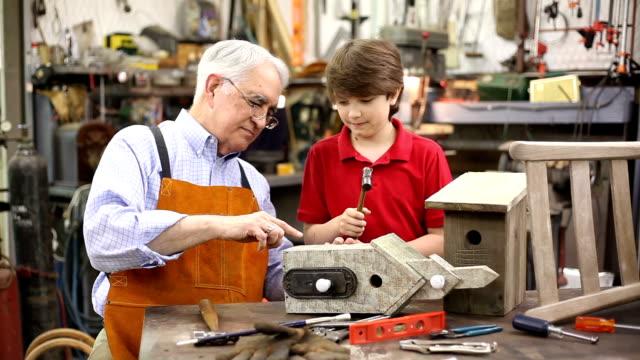 Enkel im Workshop mit Großvater ein Vogelhaus fertigzustellen.
