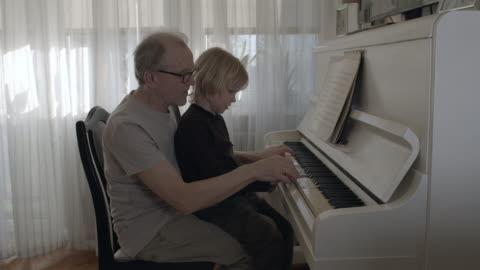 vídeos y material grabado en eventos de stock de nieto aprendiendo a tocar el piano. - nieto