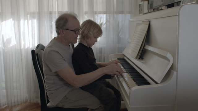 vídeos de stock e filmes b-roll de grandson learning how to play the piano. - piano