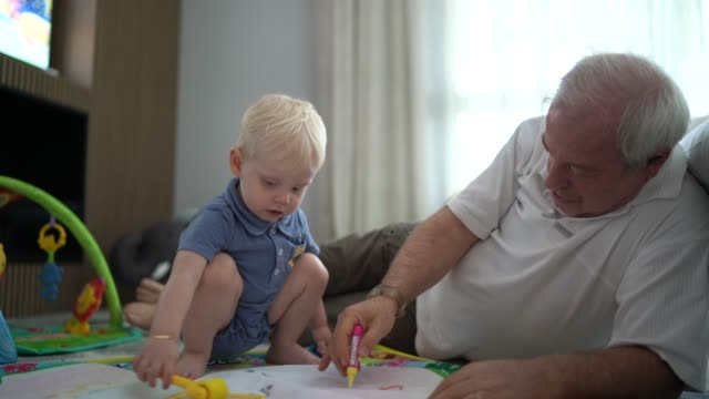 grandson playing with grandfather in the living room floor - grandson stock videos & royalty-free footage
