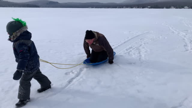 vídeos de stock e filmes b-roll de grandson pulling grandfather on sled on frozen lake in winter - puxar