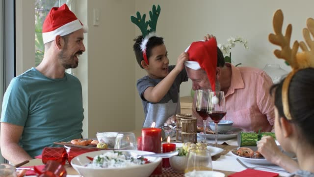grandson putting a christmas hat to his grandfather at christmas diner - father christmas stock videos and b-roll footage
