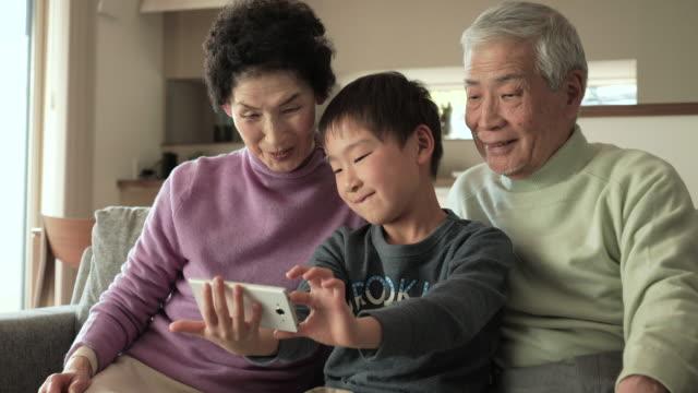 孫たファミリーの写真、スマートフォン - 団らん点の映像素材/bロール
