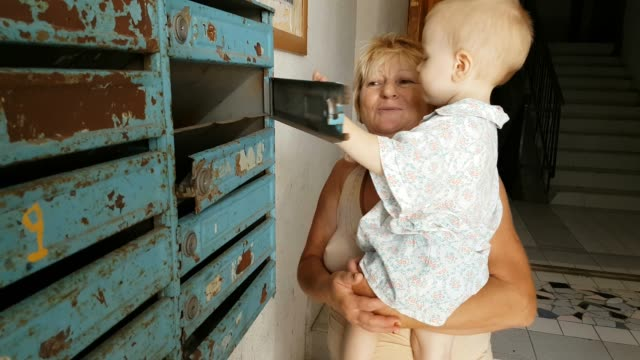 grandson with grandmother looking in mailbox - hugging self stock videos & royalty-free footage