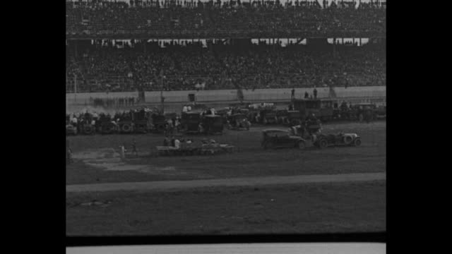 Grandstands with smoking car below / car spins out on banked turn and moves to infield another on the bank rolls down incline