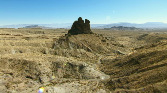 stockvideo's en b-roll-footage met a granite dike rock formation rises dramatically out of a desert landscape in big bend national park, texas. - graniet
