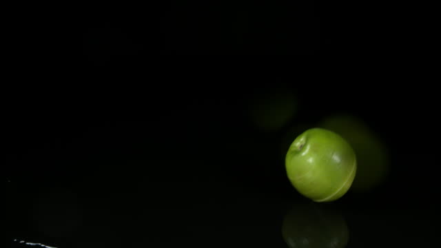 Granny Smith Apple, malus domestica, Fruit falling on Water against Black Background, Slow Motion 4K